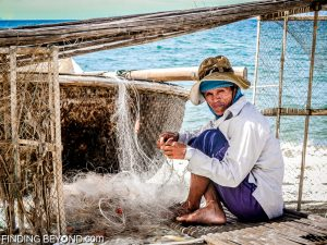 Vietnamese fisherman fixing his net.