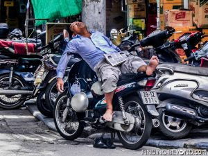 Local Vietnamese moped taxi driver fast asleep in the midday heat.